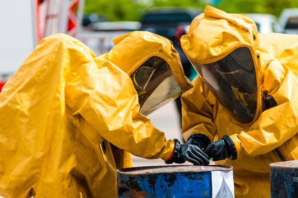 people wearing protective suits handling hazardous wastes