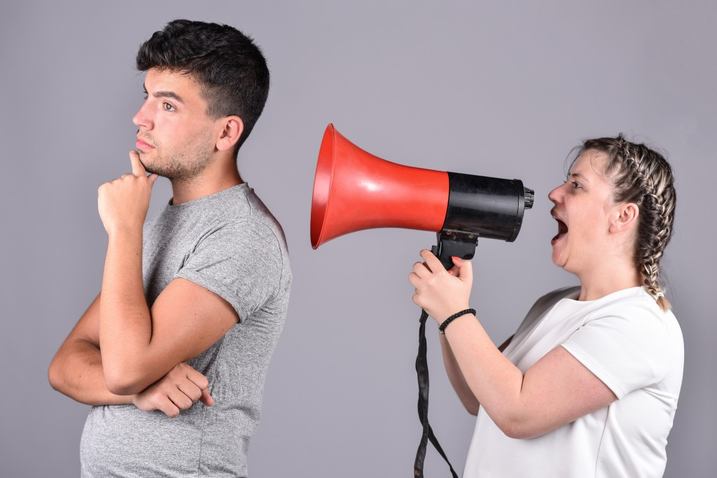 woman shouting on a megaphone infront of man